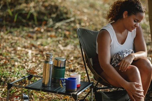 Crop young ethnic female traveler sitting on camping chair near portable table with thermoses and mugs