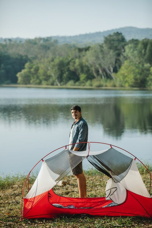 Content tourist on river shore with tent