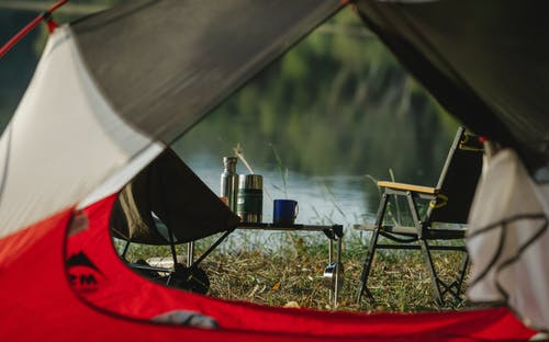 Through tent hole view of portable chairs and table with thermoses on grass shore against lake
