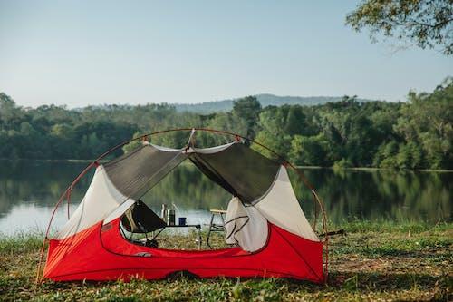 Tent on lake shore against lush trees