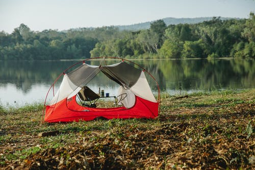 Scenery view of tent on grass coast against lake reflecting green trees under light sky on sunny day