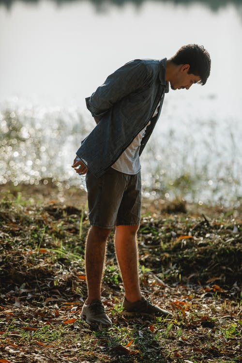Side view of male traveler in casual wear leaning forward while looking down on coast against lake