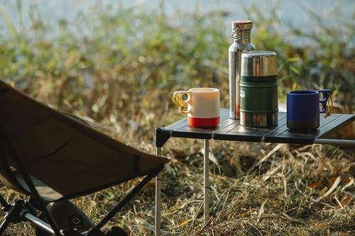 Stainless steel vacuum flasks and mugs with hot drinks on portable table near folding chair on grass shore
