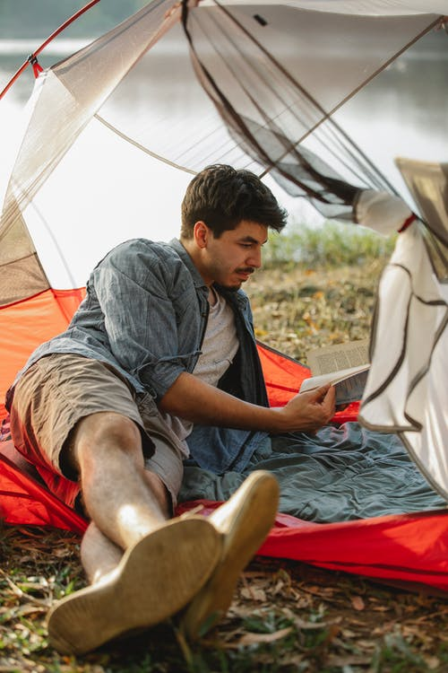 Hiker reading book in tent on river shore