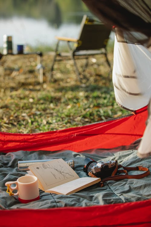 Hot drink in mug near open textbook on crumpled fabric in tent on lake shore