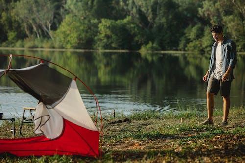 Traveler on river shore against tent during summer journey