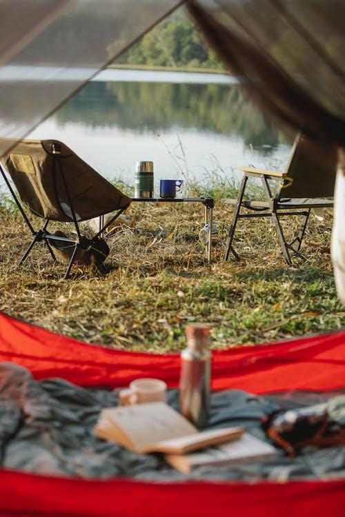 Chaise De Camping Bleu Et Noir Sur Champ D'herbe Verte Près Du Lac