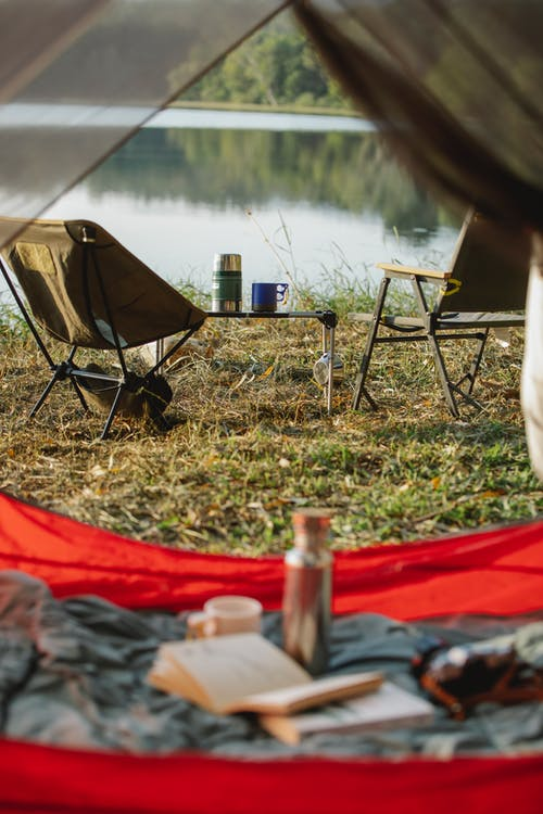 Unfolded camping chairs and tent placed on grassy lake shore in peaceful summer nature