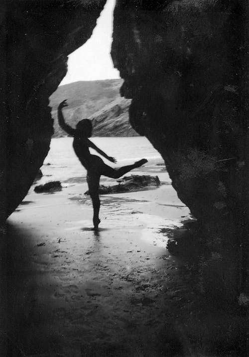 Grayscale Photo of a Person Dancing by the Seashore