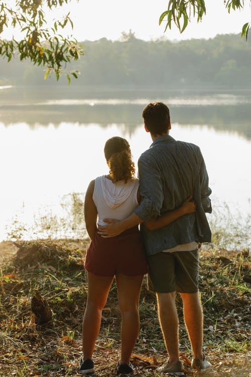 남자와여자가 물 몸 근처 갈색 바위에 서 서