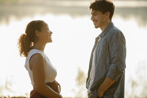 Side view of cheerful young man and Hispanic woman in casual clothes smiling and chatting while relaxing on shore of calm lake during romantic date in nature at sundown