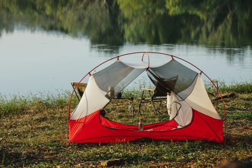 Tent and chairs placed near lake in nature
