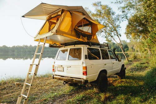 Off road car with camping tent on roof parked on grassy coast of picturesque lake surrounded by lush green trees against cloudless blue sky