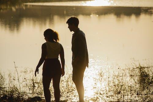 Anonymous young couple enjoying sunset on lake shore