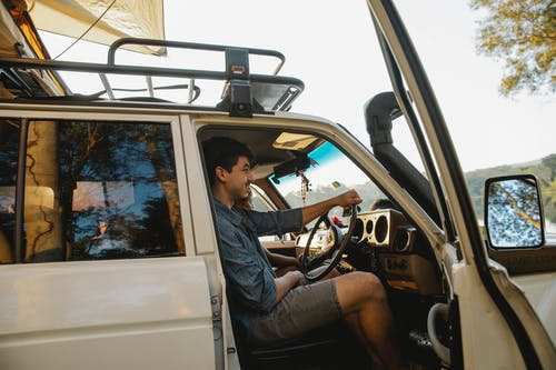 Side view of cheerful young male traveler in casual clothes smiling while driving SUV car with tent on roof during road trip in nature