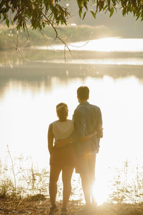 Unrecognizable couple hugging and enjoying lake view at sundown
