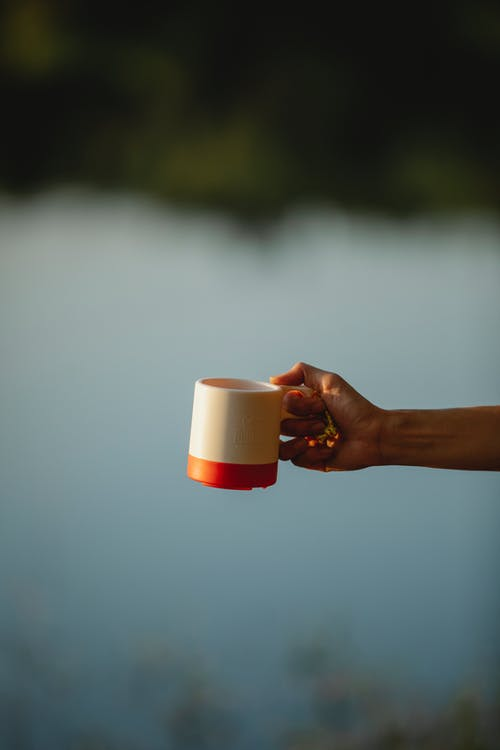 Unrecognizable woman woman holding coffee cup on lake shore