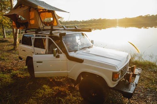 Unrecognizable young man sitting in white off road car with camping tent on top parked on grassy coast near calm lake reflecting lush trees on sunny day