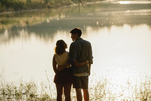 Back view of unrecognizable enamored young male and female travelers in casual clothes hugging and looking at each other while recreating on peaceful lake shore during romantic trip at sunset