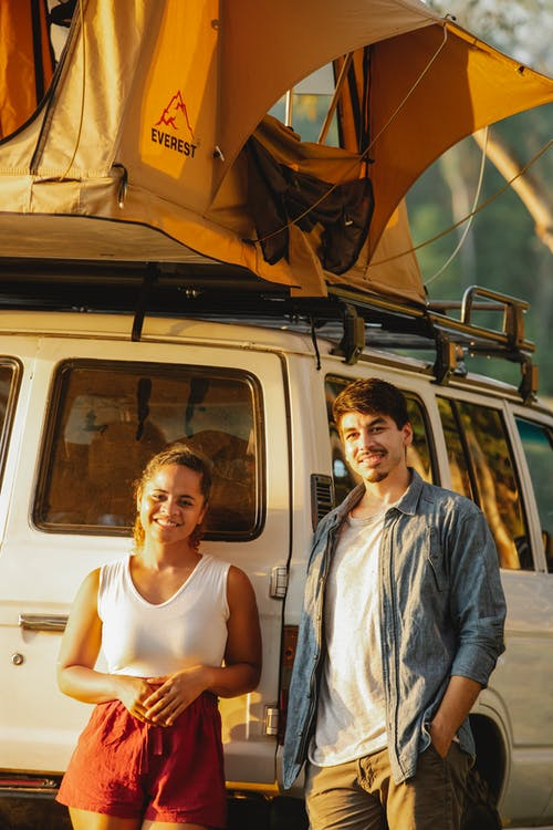 Joyful young multiracial couple smiling near SUV car and tent during camping at sunset