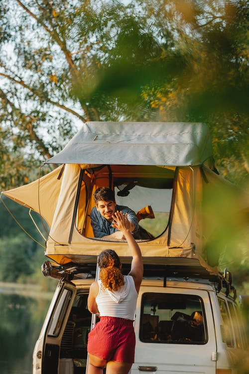 Back view of unrecognizable young female camper standing on ladder and giving high five to smiling boyfriend recreating in tent placed on SUV car roof at lakeside