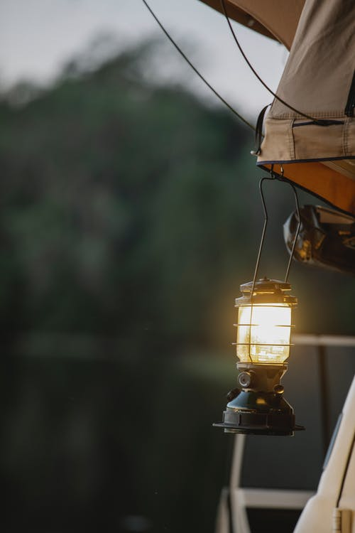Glowing vintage lamp hanging from camping tent placed on roof of car parked on lake shore reflecting lush green forest at sundown