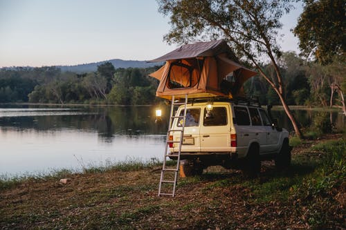 Camping tent with glowing retro lamps placed on top of white off road vehicle parked on grassy shore on peaceful lake surrounded by lush green tress against cloudless evening sky