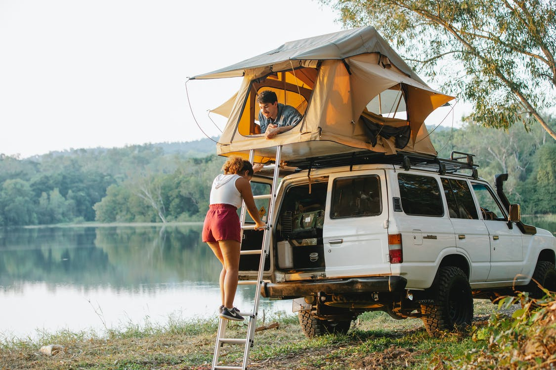 Unrecognizable woman standing on ladder near boyfriend recreating in tent during camping at lakeside