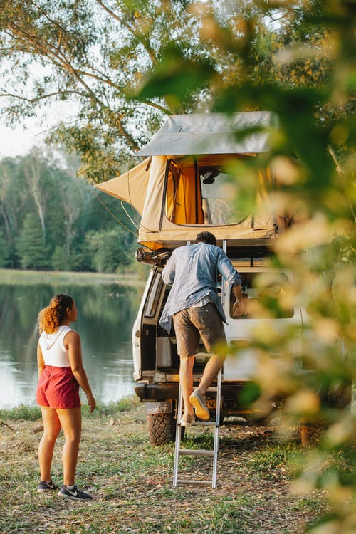 Back view of unrecognizable young male camper going downstairs from tent placed on car roof parked near lake during romantic trip with girlfriend