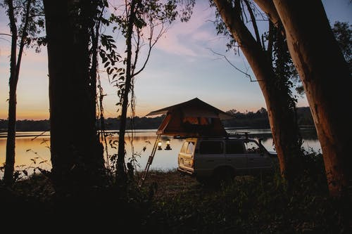 Picturesque scenery of camping tent placed on SUV car parked on coast of peaceful lake located in woods against amazing sunset sky