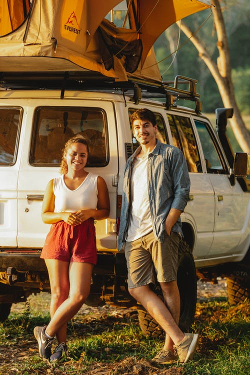 Cheerful diverse couple recreating near camping tent in green forest