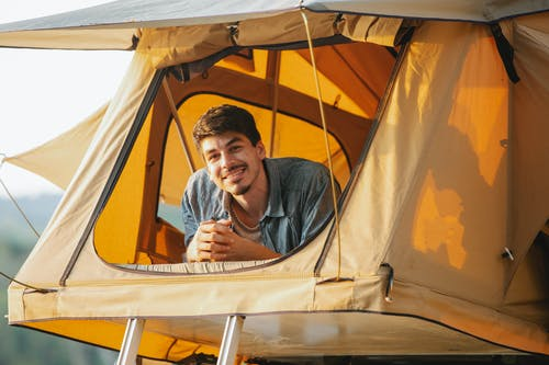 Joyful young guy smiling while relaxing in tent during camping in sunlight