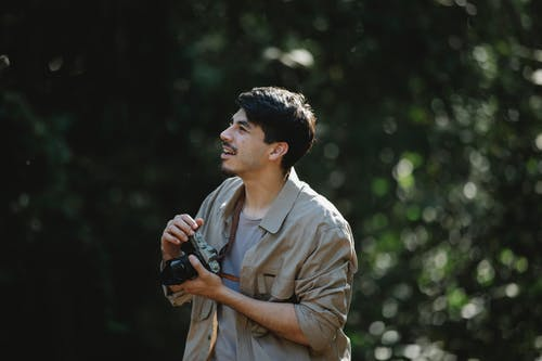 Content young bearded male traveler in casual clothes standing in lush green forest and taking photos of nature on camera on sunny day