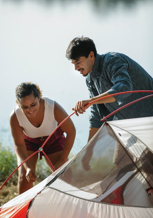 Happy young multiracial couple setting up tent on lake shore after trekking