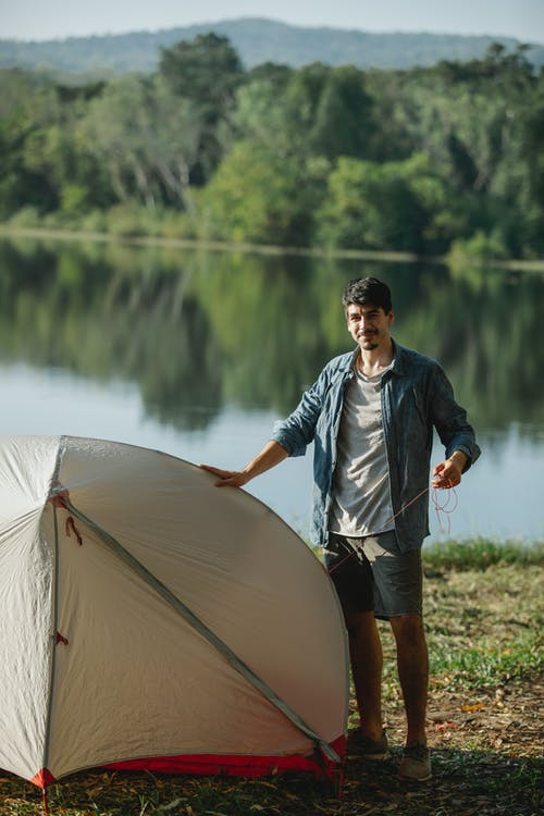 Smiling young guy setting up camping tent on lake shore after trekking