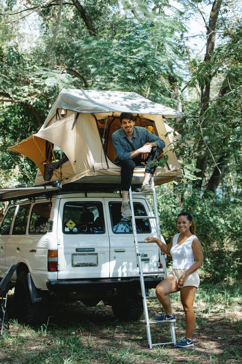 Full body of cheerful young diverse couple in casual clothes smiling while chilling together near SUV car with tent on top during camping in forest on sunny day