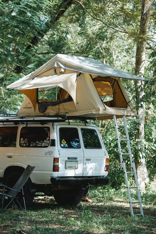SUV car with camp tent on top parked amidst lush trees in nature