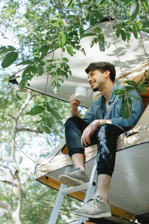 Positive man sitting in tent and drinking cup of tea in nature