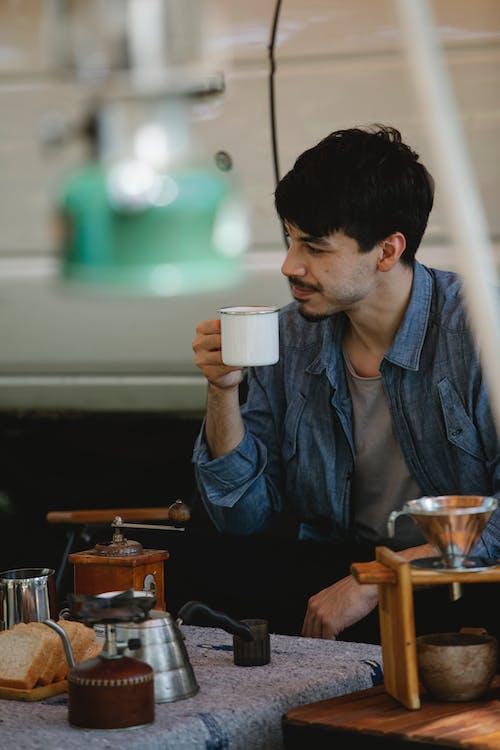 Mann In Der Blauen Jeansjacke, Die Weißen Keramikbecher Hält