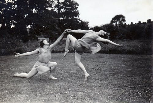 Grayscale Photo of Women Dancing on the Grass