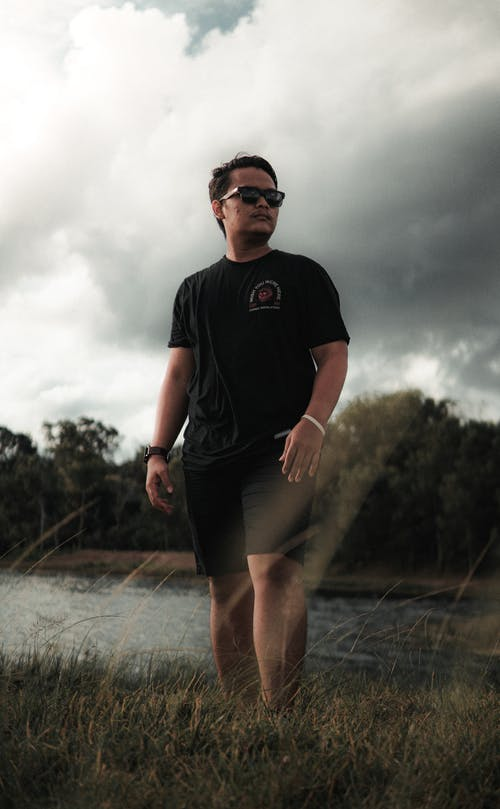 Man in Crew Neck T-shirt Standing on a Grass