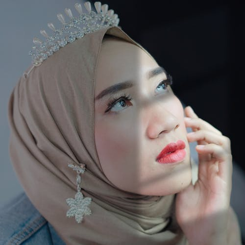 Attractive Muslim woman in hijab touching face gently