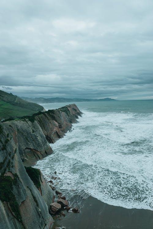 Stormy sea washing sandy coast near rocky cliff on misty day