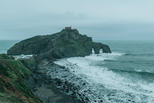 Rocky seacoast and island with church under foggy sky