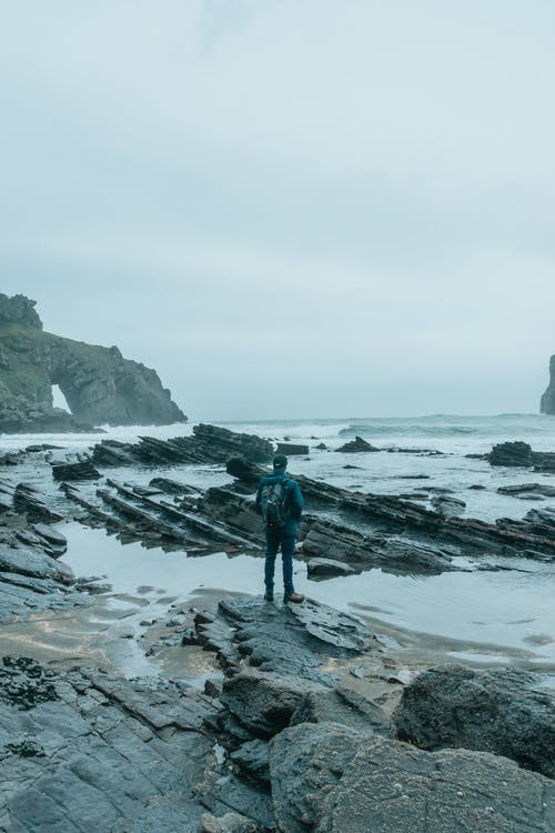 Back view of faceless male backpacker in warm outfit relaxing on wet rocky coast of waving ocean against cloudy gloomy sky in Gaztelugatxe