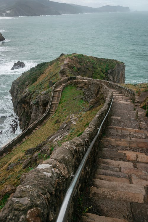 From above of curvy stone staircase leading down from San Juan de Gaztelugatxe church located on rocky island in stormy sea on cloudy day