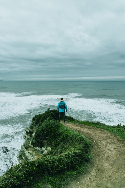 Man standing on edge of cliff above raging sea