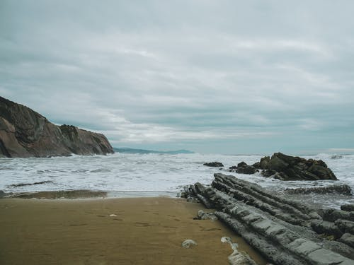 Rocky cliff in sea washing sandy beach