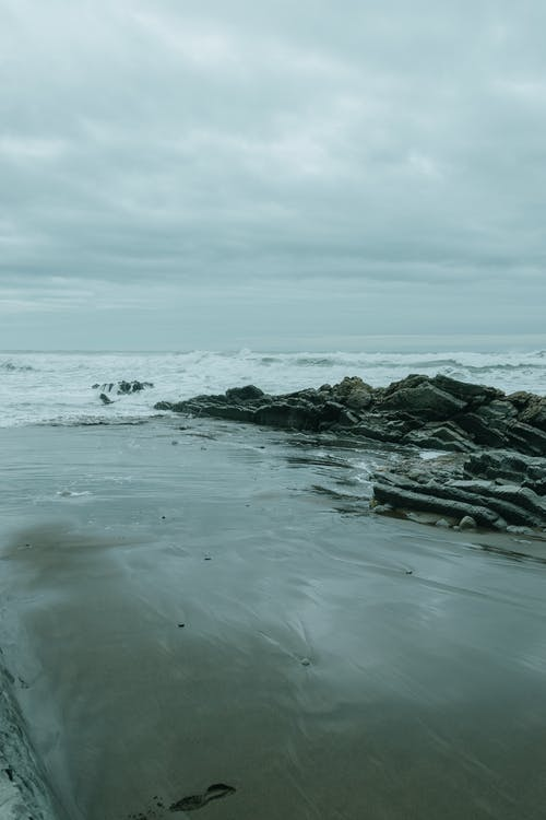 Wet sandy shore with boulders washed by sea