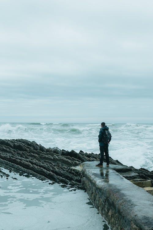Man standing on rocky coast near stormy sea